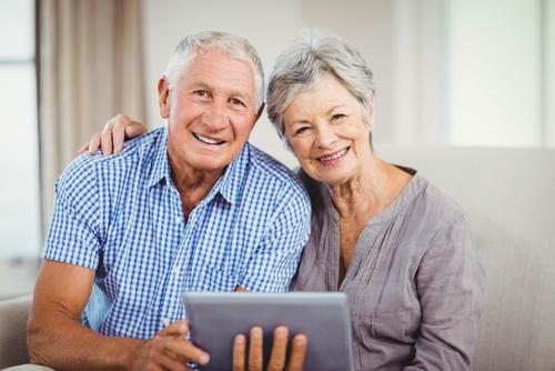 Smiling Older Couple Holding Tablet